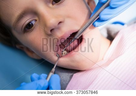 High angle view of dentist giving treatment to boy at medical clinic