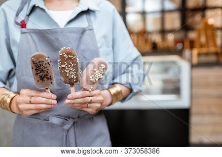 Female Seller Holding Chocolate Ice Cream On A Stick In The Shop, Close-up On Hands And Ice Cream