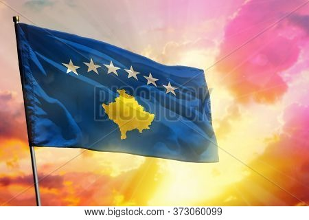 Fluttering Kosovo Flag On Beautiful Colorful Sunset Or Sunrise Background. Kosovo Success And Happin