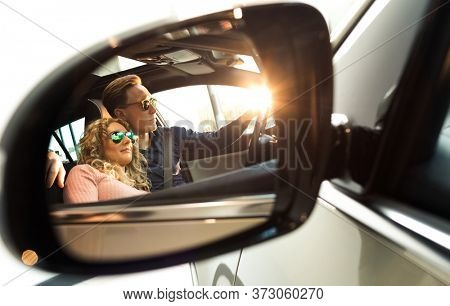 Couple reflecting in sideview mirror of car during test drive