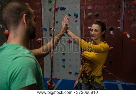 Athletes giving high five while standing by climbing wall in health club