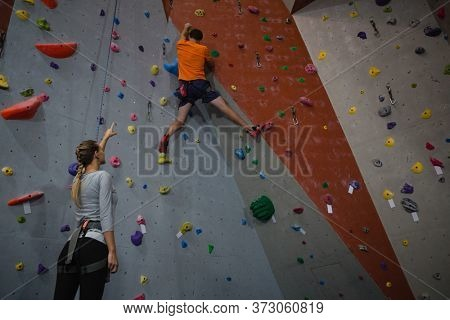 Woman instructing male athlete in climbing wall at health club