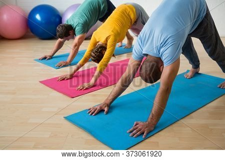 Male instructor guiding students in practicing downward facing dog pose at yoga studio