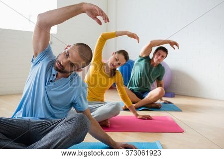 Yoga instructor with students exercising at health club