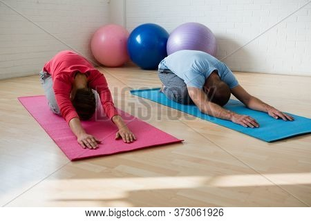 Instructor with female student practicing child pose in health club
