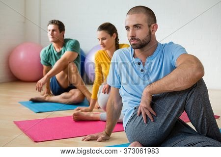Yoga instructor guiding students in practicing Ardha Matsyendrasana at health club