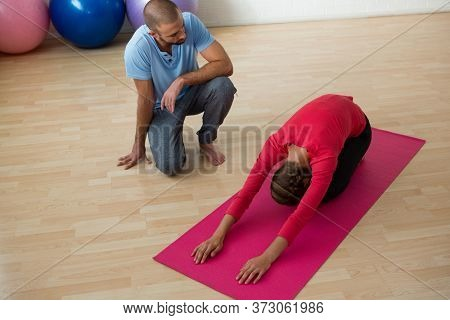 High angle view of instructor guiding student in doing child pose at yoga studio