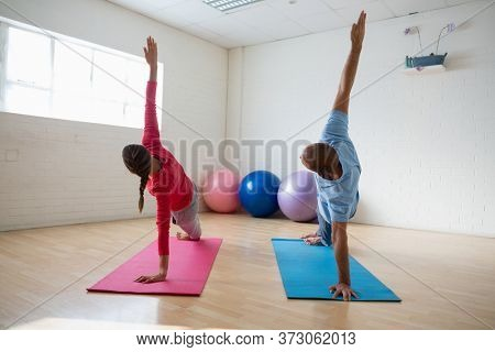 Instructor with female student practicing side plank pose in yoga studio