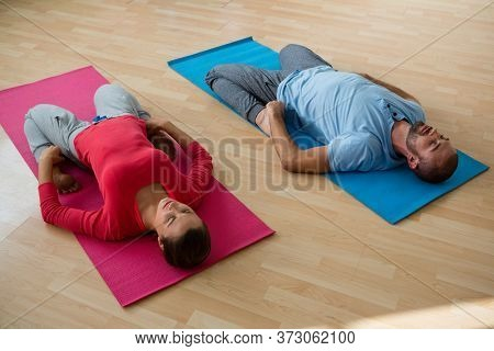 High angle view of instructor with student practicing reclined hero pose in yoga studio