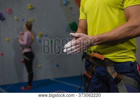Midsection of male athlete applying chalk powder to hands in health club