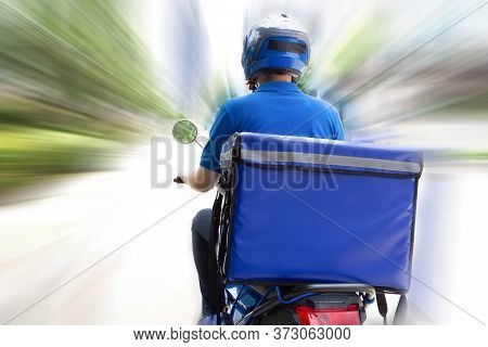 Delivery Man Wearing Blue Uniform Riding Motorcycle And Delivery Box. Motorbike Delivering Food Expr