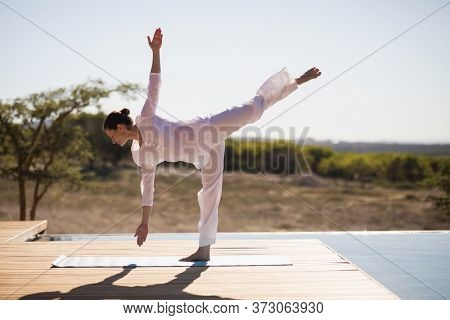 Woman practicing yoga on at poolside on a sunny day
