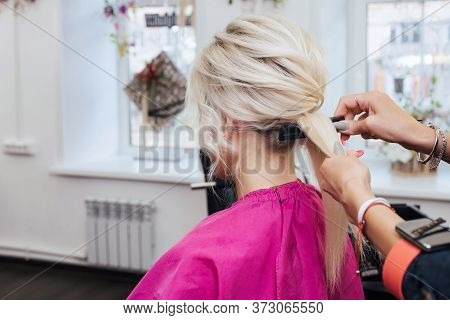 Hands Of A Professional Hairstylist Make A Hairstyle For A Blonde Girl With Long Hair