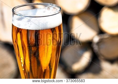 A Full Glass Of Fresh Beer. Beer Glass And Timber. A Glass With Light Beer On The Background Of Wood