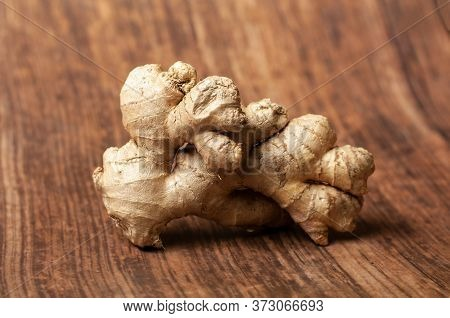A Raw Ginger Wood With Shiny Peel On A Brown Wooden Background