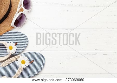 Summer vacation items and accessories. Flip flops, sunglasses and sun hat on wooden table. Top view flat lay with copy space
