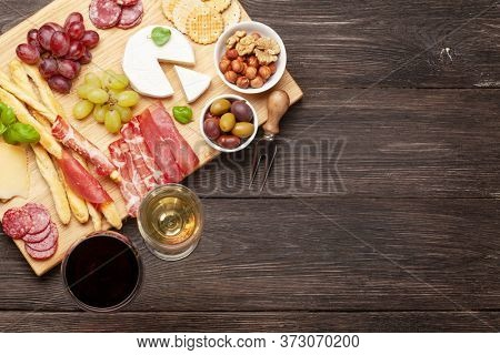 Cheese, meat, grapes and olives antipasto. Appetizer selection plate and glasses with red and white wine. Top view with copy space. Flat lay