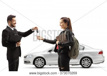 Car salesman giving car keys from a silver car to a young female student isolated on white background
