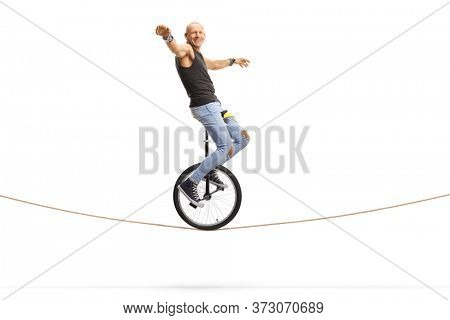 Bald man hipster balancing a unicycle on a rope isolated on white background