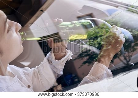An Unrecognizable Female Drinking Beer While Driving Car. Concepts Of Driving Under The Influence, D