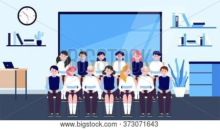 School Students Posing For Class Photo In Classroom. Teen Boys And Girls In Uniforms Sitting In Rows