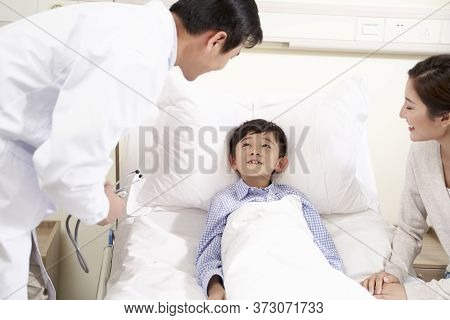 Five Year Old Asian Child Lying In Bed In Hospital Ward Accompanied By Mother Talking To Doctor