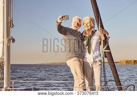 Happy Senior Couple Standing On The Side Of Sail Boat Or Yacht Deck Floating In Sea. Man And Woman S