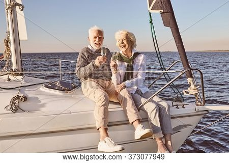 Happy Senior Couple Sitting On The Side Of Sail Boat Or Yacht Deck Floating In Sea. Man And Woman Dr