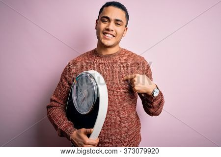 Young brazilian man doing diet to lose weigth holding scale over isolated pink background with surprise face pointing finger to himself