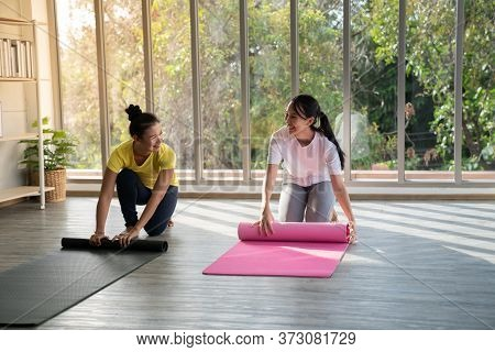 Two Happy Asian Women In Yoga Poses In Yoga Studio With Natura Llight Setting Scene / Exercise Conce