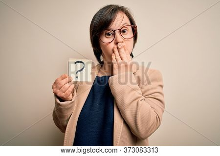 Young down syndrome business woman holding question mark paper as doubt symbol cover mouth with hand shocked with shame for mistake, expression of fear, scared in silence, secret concept