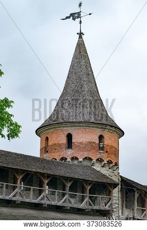 Castle Tower With Forged Weather Vane And Covered Walkways Around The Perimeter Of The Walls. Mediev