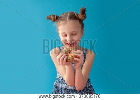 7 Year Old Girl Rejoices At The Donut. She Is In Anticipation. She Is Enjoys. Hairstyle. On A White