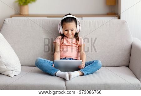 Asian Girl Using Tablet Computer Wearing Wireless Headphones Watching Cartoons Sitting On Couch At H