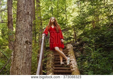 The Young Woman In Red Dress In Old Stairs In Forest. Concept Of Nature And Happy Life, Adventure. B