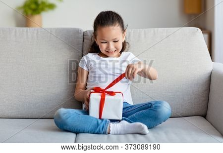 Birthday Girl. Happy Asian Kid Opening Gift Box Celebrating Holiday Sitting On Couch At Home.
