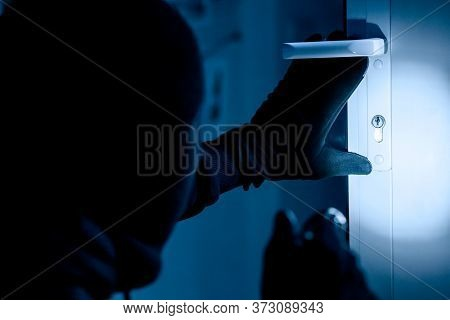 Vandalism Concept. Rear View Of Disguised Burglar Entering Enclosed Property, Holding Flash Light, L