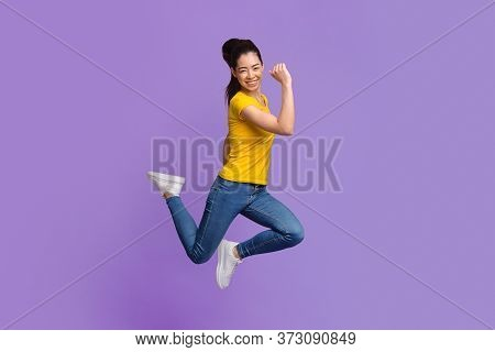 Overjoyed Asian Girl Jumping In The Air, Celebrating Success With Raised Fists Over Purple Studio Ba