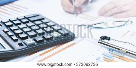 Finance And Business Concept. Hand With Calculator On Financial Graphs On Desk With Specs Or Eyeglas