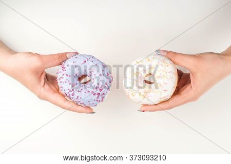 Woman Hands Holding Donuts, Top View. Girl Making Choice. Sweet Donuts For You. Background With Copy
