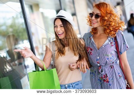Happiness, Friends, Shopping And Fun Concept-smiling Young Women With Shopping Bags.