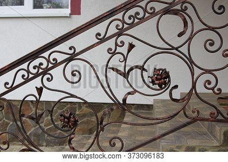 Stairs With Wrought Iron Railings, Ornament With Many Details With A Flower Forged On The Railing