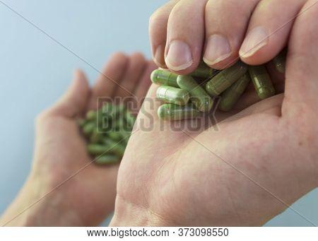 Chlorella In Capsules Super Food. Vegetable Dietary Supplement Chlorella.capsules In Hands Top View