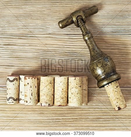 Vintage Metal Corkscrew And Corks From Wine Bottles On A Wooden Background With Copy Space. Wine Cor