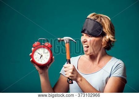 A Portrait Of Angry Woman With Sleep Mask On Head Holding Hummer Wanted To Crush Alarm Clock In The