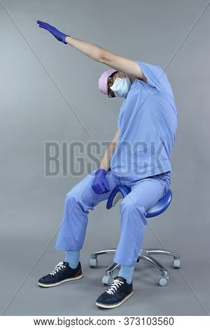 Exercise for dentist on chair in sitting position.Caucasian dentist in uniform, mask and eyeglasses , stretching arm, neck and back   in studio - healthy lifestyle at work.