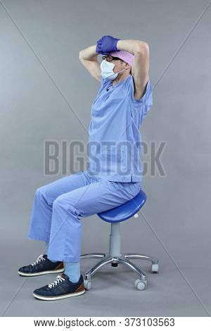 Exercise for dentist on chair.Caucasian dentist in uniform, mask and eyeglasses , stretching arms  and back   in studio - healthy lifestyle at work.