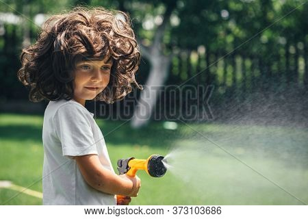 fun child plays with water in the backyard in the garden