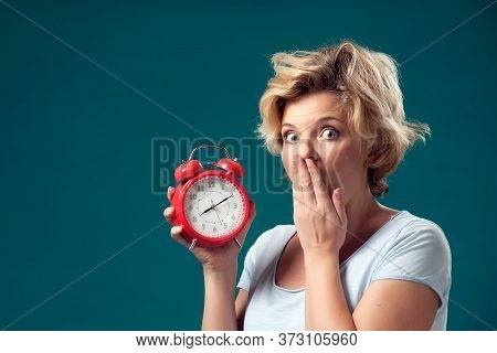 A Portrait Of Woman With Short Blond Hair Holding Red Alarm Clock And Feeling Shocked Because Of Ove