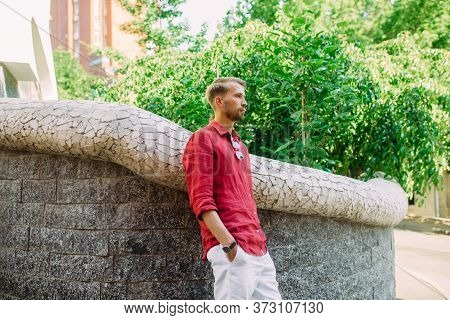 Young Man In Shorts And Shirt Stands And Ponders Near Wall At Street.